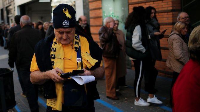 Un home amb llaç groc, samarreta groga i bufanda groga vota aquest 21D a Barcelona (Reuters)