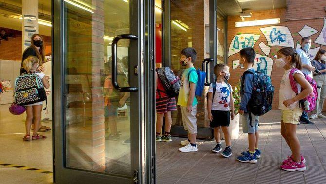 Un grup de nens fa cua per entrar a l'escola Catalonia de Barcelona (EFE/Enric Fontcuberta)