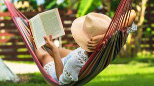 Una dona llegeix un llibre en una hamaca