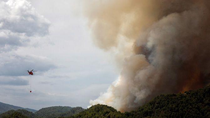 Un helicòpter treballa en l'extinció de l'incendi a la serra de Miralles (EFE/Susanna Sáez)