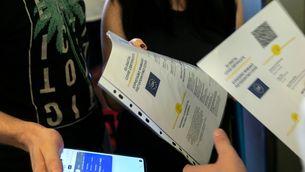 Un membre de la tripulació comprova el certificat digital Covid de la UE als passatgers que pugen a un vaixell al port del Pireu, a Grècia, el juliol del 2021 (Horitzontal)