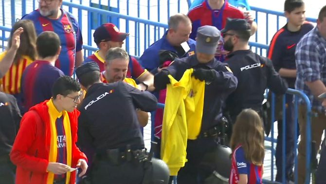 Un policia escorcolla un aficionat del Barça i inspecciona una samarreta groga