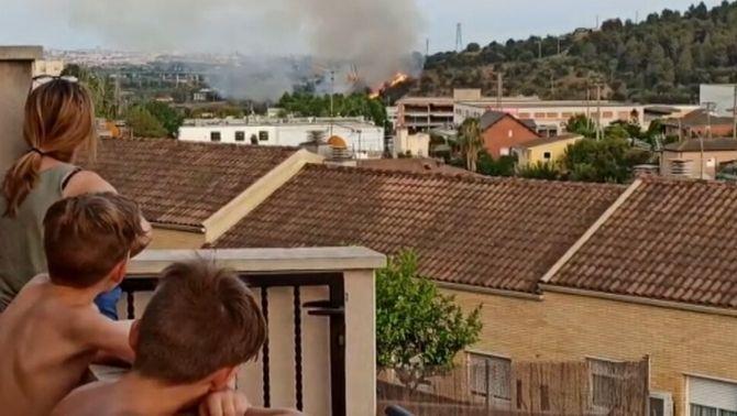 Tres persones observen el foc de Sant Vicenç, prop de les cases