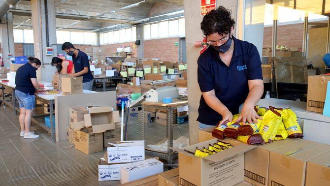 Usuaris del centre ocupacional de la Fundació Els Joncs preparant els lots de menjar. Imatge publicada el 2 d'agost del 2021 (Horitzontal)