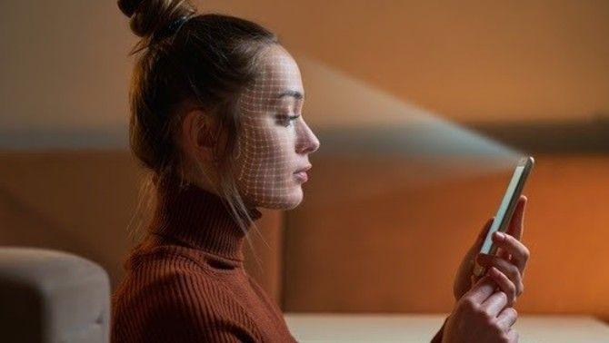 Una noia fa servir la tecnologia de reconeixement facial amb el telèfon mòbil
