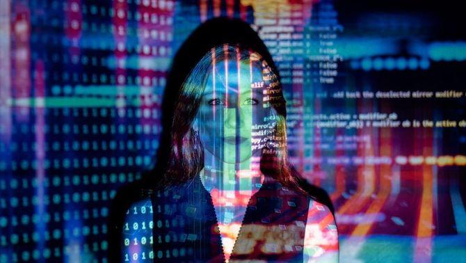 Paraules, colors i dades d'una pantalla es projecten sobre la cara d'una dona