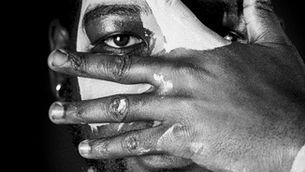 Noi negre amb una mà a la cara