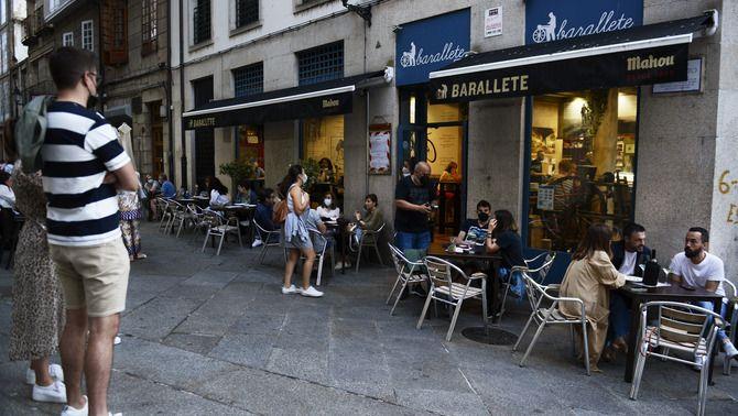 Gent a les portes i a la terrassa d'un bar a Ourense, al juliol