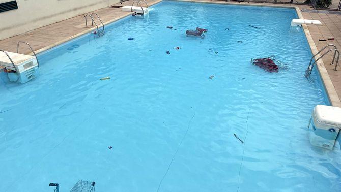 La piscina de la Vila Universitària amb brutícia i tres carros de supermercat a l'aigua després del macrobotellon