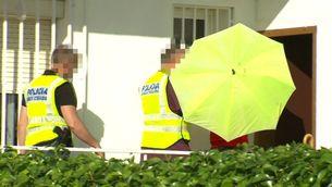La detinguda, amagada darrere un paraigua, durant la inspecció ocular casa seva