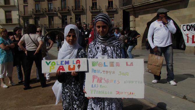Dues noies immigrades mostren pancartes demanant pau. (Foto: ACN)