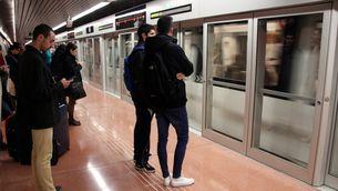 Usuaris de la nova L9 sud del metro esperant l'arribada d'un comboi a la parada de Zona Universitària (ACN)