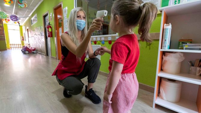 Una mestra pren la temperatura a una nena en una llar d'infants (EFE/Marcial Guillén)