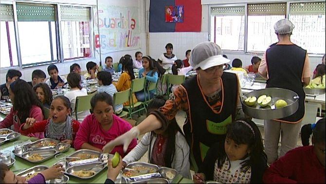 Menjador escolar amb els monitors repartint el menjar