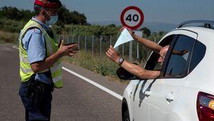 Un veí del Segrià mostra el certificat d'autoresponsabilitat a un agent en un control dels Mossos (EFE/Ramón Gabriel)
