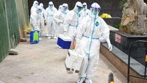Treballadors sanitaris amb vestits de protecció per fer tests a la província xinesa de Hunan