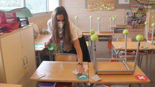una mestra amb mascareta neteja les taules d'una aula escolar