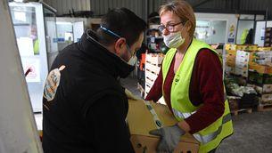 Una voluntària del Banc dels Aliments recull una caixa de productes frescos d'empreses de Mercabarna (ACN)