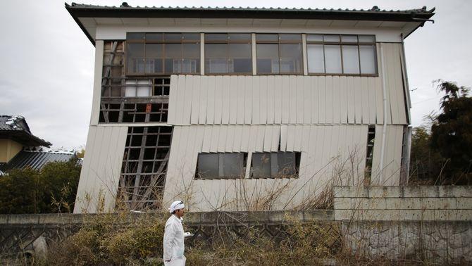 Norio Kimura, de 49 anys, que va perdre al seu pare, dona i filla pel tsunami, camina davant d'una casa danyada dins de la zona d'exclusió…