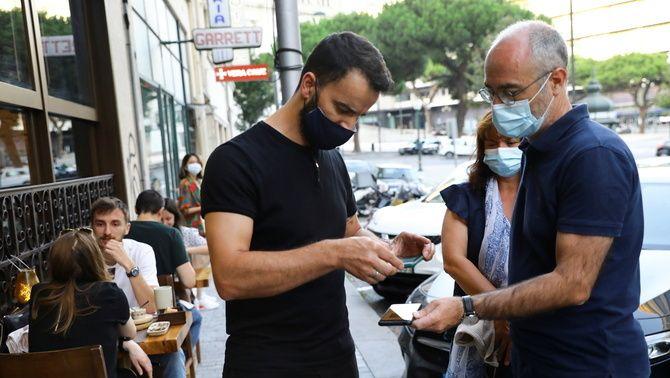 Un cambrer valida el certificat Covid d'un client a l'entrada d'un restaurant a Porto