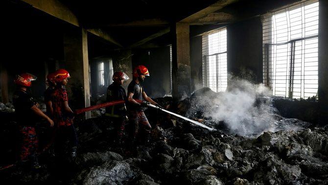 Els bombers continuen remullant les cendres dins l'edifici cremat i busquen els cossos dels treballadors que hi van quedar atrapats