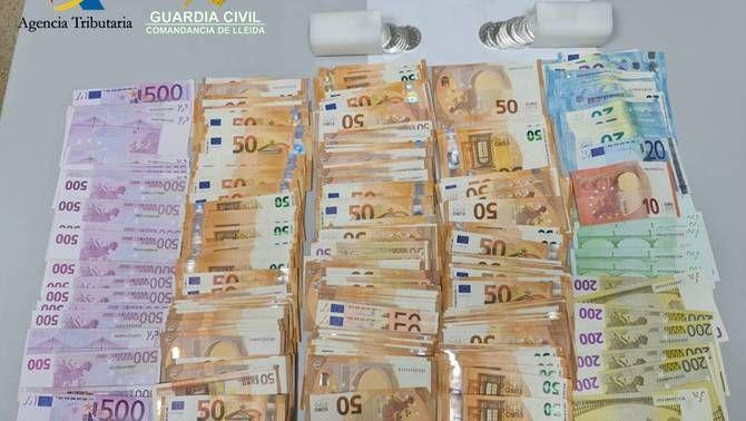 Pla de detall dels diners i les monedes de col·lecció decomissades per la Guàrdia Civil a la duana de la Farga de Moles, a les Valls de Valira (Alt Urgell). Imatge facilitada el 16 de febrer de 2021 (