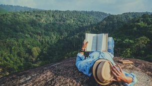 Home llegint amb vistes al bosc