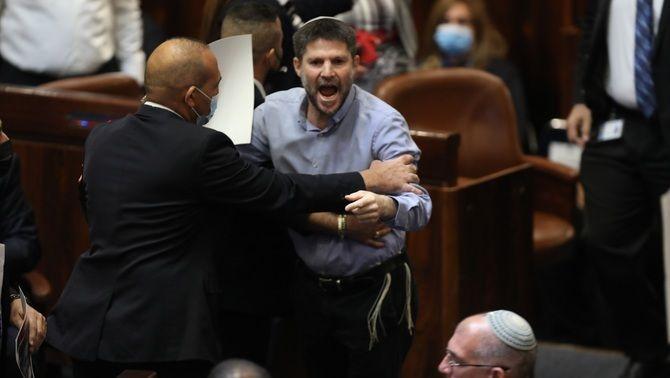 El diputat Betzalel Smotrich, del Partit Sionista Religiós, escortat per membres del Parlament després de ser expulsat