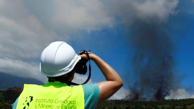 Un membre de l'Institut Geològic observa el fum i la lava que surt de l'erupció a Cumbre Vieja