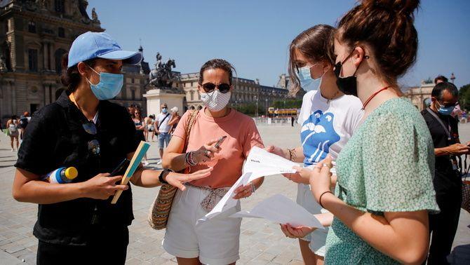 Un agent de seguretat comprova els passis dels visitants davant del museu del Louvre, a París