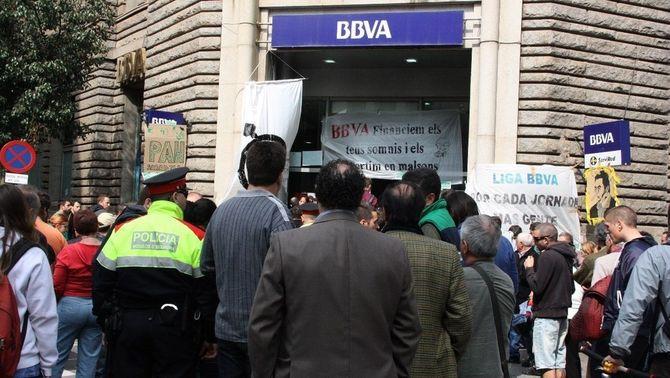 Una gran multitud s'ha aplegat davant l'oficina del BBVA en el moment de la sortida dels activistes. (Foto: ACN)