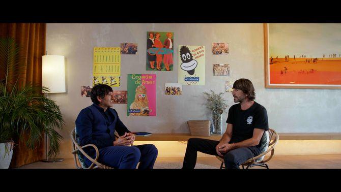 Millán conversa amb Parreño amb cartells de fons d'espectacles de La Cubana