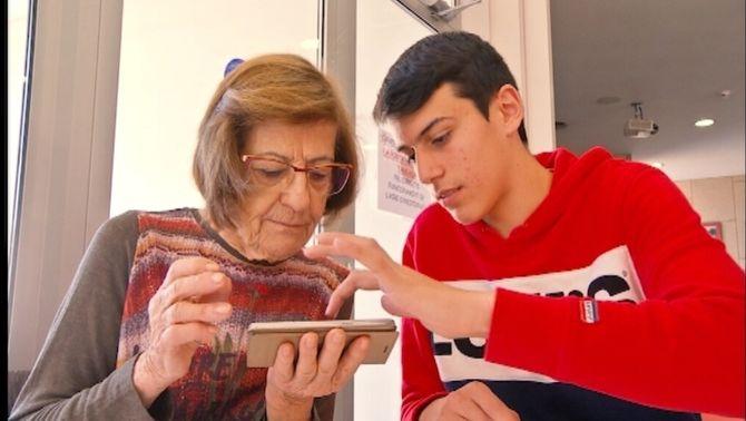 Estudiants que ajuden la gent gran a fer anar els mòbils