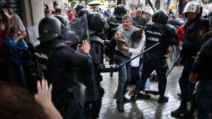 Un home intenta protegir una dona de les càrregues dels antiavalots, l'1 d'octubre a Barcelona (ACN / Jordi Play)