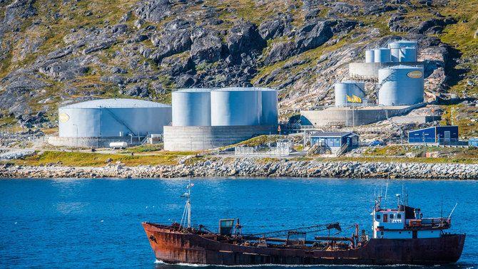 Dipòsits de combustible a la costa, amb un vaixell en primer pla