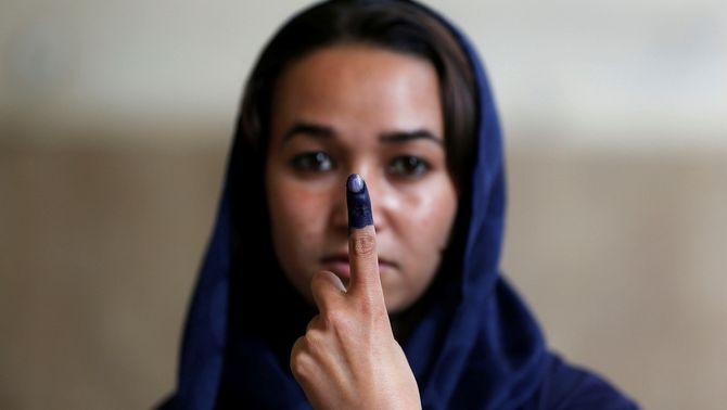 Una dona afganesa mostra el dit tacat de tinta després de votar a les eleccions presidencials al país