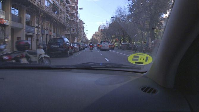 Un vehicle amb l'etiqueta groga circulant per Barcelona