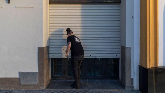 El propietari d'un local abaixa la persiana per les restriccions per la Covid (Europa Press / María José López)