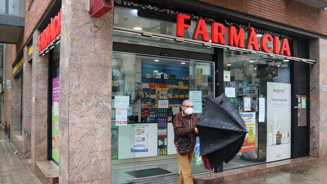 Un home amb mascareta sortint d'una farmàcia