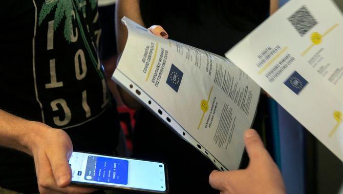 Un membre de la tripulació comprova el certificat digital Covid de la UE als passatgers que pugen a un vaixell al port del Pireu, a Grècia, el julio…