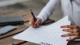 Una dona consulta un calendari de paper