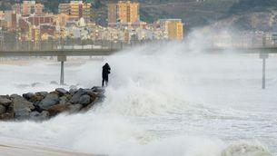 Un fotògraf intenta captar l'estat de la mar amb el Pont del Petroli de fons, a Badalona (Lluís Rodríguez)