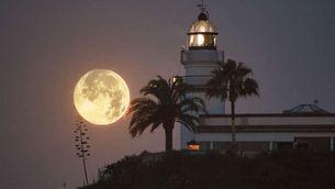 La Lluna al costat del far de Calella. (Foto: Tino Valduvieco)
