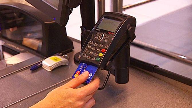 Una persona paga amb una targeta de crèdit.