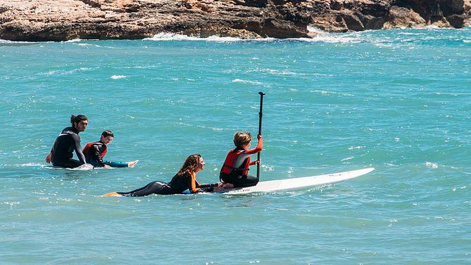 Pla obert de diversos monitors fent teràpia de surf amb nens autistes dins l'aigua a la platja de Sitges. Imatge del 4 de juny de 2017 (horitzo…