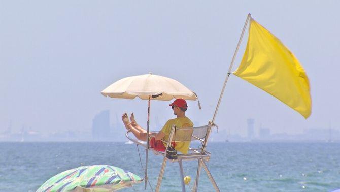 Bandera groga en desenes de platges de la costa central per aigua tèrbola