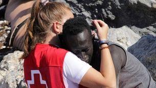 Abraçada entre un migrant i una cooperant de la Creu Roja en un dels espigons fronterers de Ceuta (EFE / Reduan)