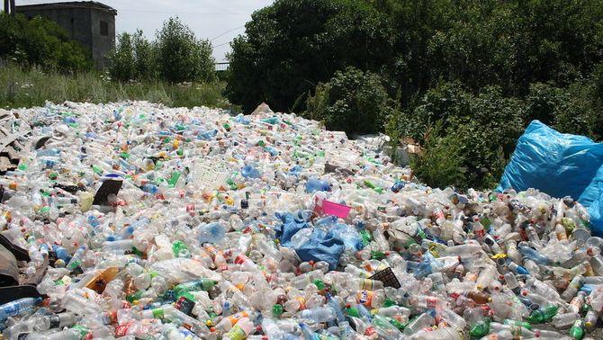 Gran pila de residus plàstics en un entorn natural