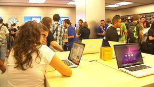 Dos joves miren un MacBook a la nova botiga Apple de Barcelona.