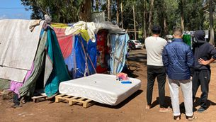 Els veïns s'acosten al campament i porten menjar als joves migrants